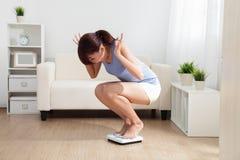 La mujer trastornada encendido pesa la escala Foto de archivo libre de regalías