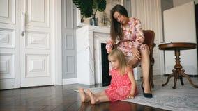 La mujer trenza la trenza de su pequeña hija almacen de metraje de vídeo
