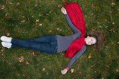 La mujer triguena está en la bufanda roja que miente en la hierba. Imágenes de archivo libres de regalías