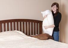 La mujer triguena hace la cama Fotografía de archivo libre de regalías