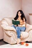 Mujer encrespada para arriba en una lectura de la butaca Imagenes de archivo