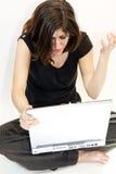 La mujer triguena joven consigue malas noticias en el ordenador Foto de archivo