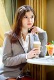 La mujer triguena joven está bebiendo el coffe Foto de archivo libre de regalías