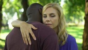 La mujer triste abraza al novio negro, preocupante debido a la desaprobación de la familia almacen de video