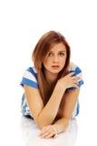 La mujer triste adolescente miente en el piso Fotografía de archivo