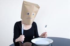 La mujer triste anónima con vacío plat se sienta en la tabla solamente Fotos de archivo