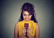 La mujer triste cansó de restricciones de la dieta que anhelaba la barra de chocolate de dulces Foto de archivo libre de regalías