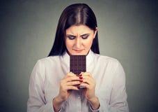 La mujer triste cansó de restricciones de la dieta que anhelaba la barra de chocolate de dulces Imagenes de archivo