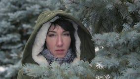 La mujer triste está presentando en bosque del invierno y está ocultando detrás de ramas de árbol de abeto metrajes