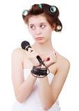 La mujer triste joven en una toalla de baño y bigudíes de pelo con sus manos ató el micrófono del alambre Imágenes de archivo libres de regalías