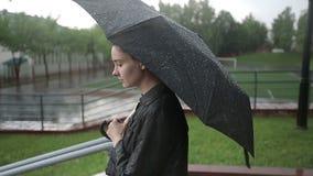 La mujer triste sola camina abajo de la calle en fuertes lluvias Cámara lenta