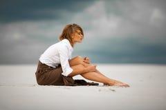 La mujer triste y pensativa joven se sienta en la arena en desierto Foto de archivo libre de regalías