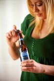 La mujer tuerce el casquillo apagado de la botella de Bud Light Bud Light Is Produc Fotos de archivo libres de regalías