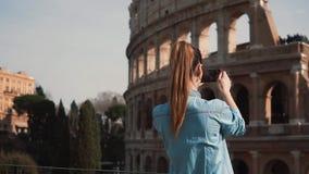 La mujer turística corre abajo de la calle en Roma, Italia, toma imágenes de Colosseum La muchacha mira las fotos Cámara lenta almacen de video