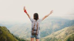 La mujer turística feliz joven de la visión trasera con la mochila aumenta los brazos abiertos en el aire en el Mountain View épi almacen de metraje de vídeo