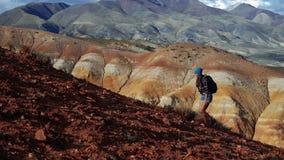 La mujer turística joven con la mochila y el sombrero sube para arriba la montaña de piedra roja Hay paisaje escénico y nublado i almacen de metraje de vídeo