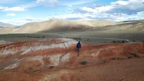 La mujer turística joven con la mochila y el sombrero sube para arriba la montaña de piedra roja Hay paisaje escénico y nublado i almacen de video