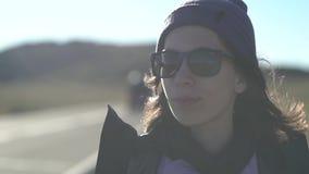 La mujer turística joven con una mochila y las gafas de sol está intentando coger la señal del teléfono en un camino de la montañ metrajes