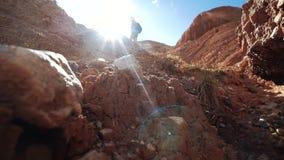 La mujer turística joven en pantalones cortos y casquillo con una mochila se está colocando en un pico de montaña rojo en los ray almacen de metraje de vídeo