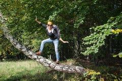 La mujer turística joven está llevando a cabo un equilibrio en la rama del abedul Foto de archivo