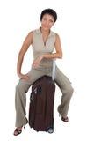 La mujer turística joven se sienta en la maleta aislada Imagen de archivo