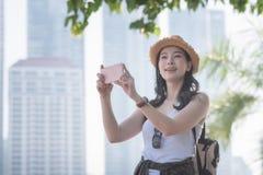 La mujer turística a solas asiática hermosa goza el tomar de la foto por el teléfono elegante en el punto de visita turístico de  imagen de archivo libre de regalías
