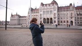 La mujer turística toma imágenes cerca del parlamento en Budapest en otoño o invierno almacen de video