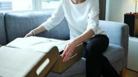 La mujer unboxing desempaquetando los nuevos zapatos de la ropa compró en línea almacen de metraje de vídeo