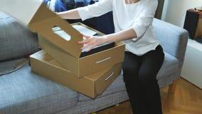 La mujer unboxing desempaquetando los nuevos zapatos de la ropa compró en línea metrajes