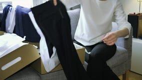 La mujer unboxing desempaquetando la nueva ropa compró a Massimo Dutti en línea metrajes