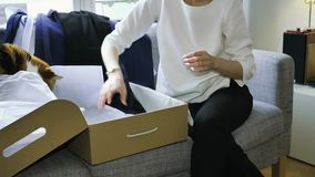 La mujer unboxing desempaquetando la nueva ropa comprada en línea ayudó por su gato metrajes