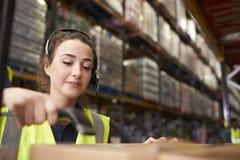 La mujer utiliza al lector del código de barras en un almacén, un principal y hombros imagenes de archivo