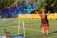 La mujer utiliza el agua jabonosa para crear la burbuja enorme en el festival Imagen de archivo libre de regalías