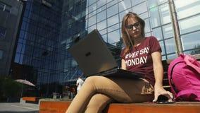 La mujer utiliza el ordenador portátil al aire libre almacen de video