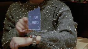 La mujer utiliza el reloj del holograma con el texto aprende francés almacen de video