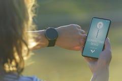 La mujer utiliza el smartwatch y el teléfono elegante fotografía de archivo libre de regalías