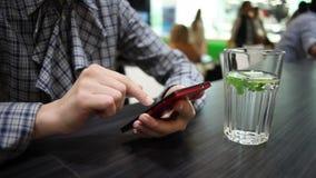 La mujer utiliza el teléfono y bebe el agua en café almacen de metraje de vídeo