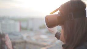 La mujer utiliza los vidrios de una realidad virtual en el tejado