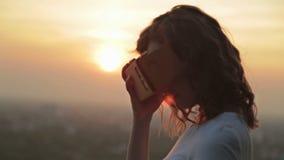 La mujer utiliza los vidrios de una realidad virtual en la puesta del sol