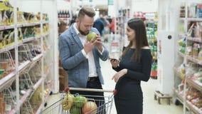 La mujer utiliza smartphone a la lista de verificaci?n de productos y el hombre elige las frutas y las huele en supermercado almacen de video