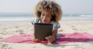 La mujer utiliza una tableta en la playa