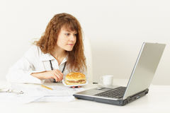 La mujer va a comer el emparedado de la cena en la oficina Fotografía