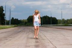 La mujer va en una carretera. Foto de archivo