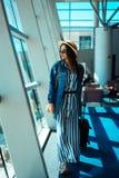 La mujer va viaje con la caja del traje en el aeropuerto Foto de archivo libre de regalías