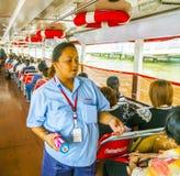 La mujer vende boletos en un transbordador en el río Chao Phraya en Bangkok Foto de archivo libre de regalías