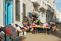 La mujer vende mercancías de mano de los secons en la calle en el Medina de Sfax, Túnez fotografía de archivo