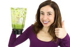 La mujer verde feliz del smoothie manosea con los dedos para arriba Foto de archivo