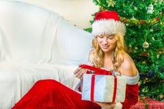 La mujer vestida como Papá Noel abrió un regalo fotografía de archivo