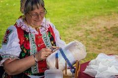 La mujer, vestida en traje popular, hace el cordón tradicional de la bobina Foto de archivo