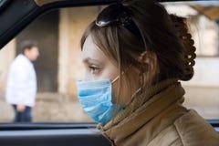La mujer viaja en el automóvil en una máscara protectora Imagen de archivo